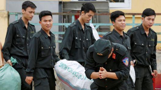 Một cảnh sát cúi đầu cảm tạ dân làng Đồng Tâm sau khi được phóng thích hôm 22 tháng Tư